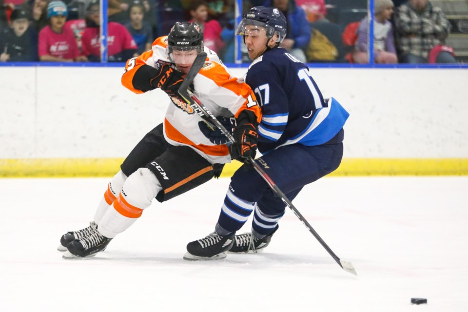 Drumheller Dragons Shane Ott is hooked by the Canmore Eagles Cameron Chin as he drives to the net during a game at the Canmore Recreation Centre. EVAN BUHLER RMO PHOTO