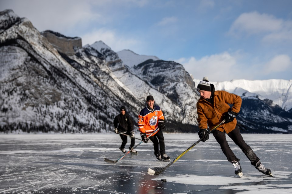 Hans Vivian, right, Ryan Hunter and James Johnston play a game of keep away on Lake Minnewanka on Thursday (Jan. 2). EVAN BUHLER RMO PHOTO