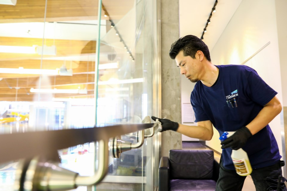 Joe Harasaki an Elevation Place employee sanitizes a hand rail at Elevation Place in response to the novel coronavirus on Friday (March 13). EVAN BUHLER RMO PHOTO⁠