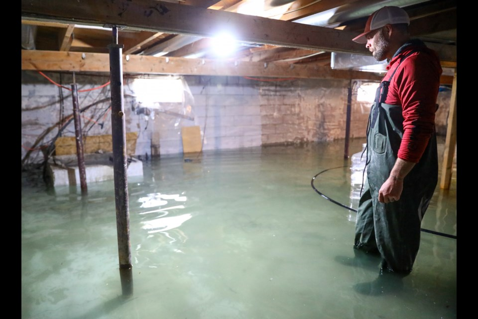 Exshaw resident Brent Peters stands in his basement after it was flooded with more than 14 inches of water June 2. Peters said water continued to flow into the basement, and expected the room to flood completely within a few days. Flooding issues started more than 10 days prior. EVAN BUHLER RMO PHOTO⁠