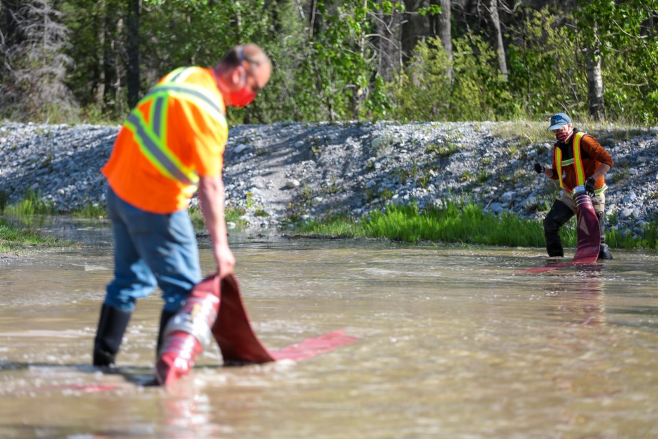 Municipal District of Bighorn workers connects hoses to drain flood waters in Exshaw on Tuesday (June 2). Flooding issues started more than 10 days ago and more than 25 homes have been affected in the hamlet. EVAN BUHLER RMO PHOTO
