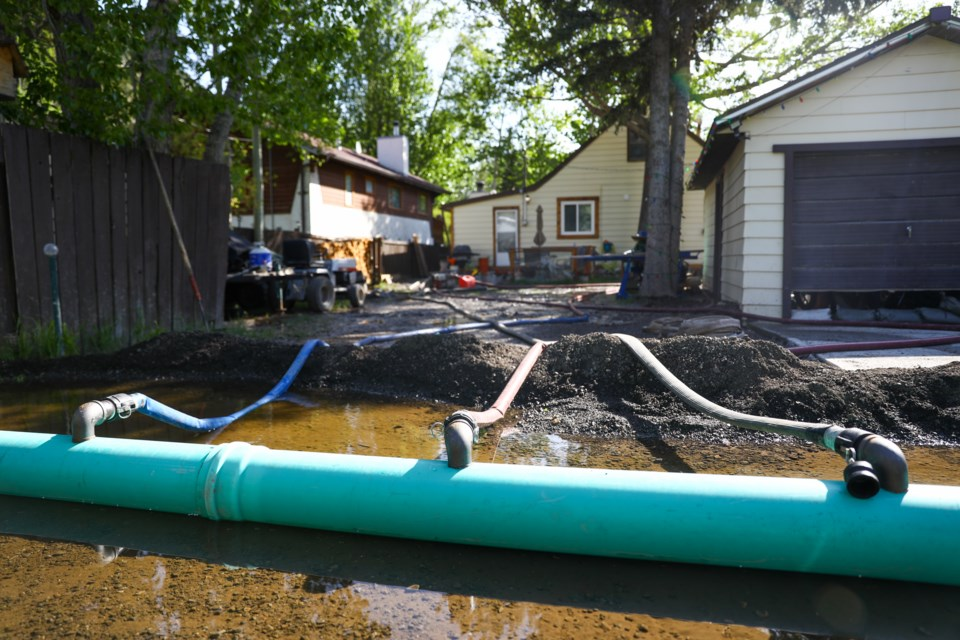 Water hoses from Exshaw residents homes are funnelled into an irrigation pipe, set up by the MD of Bighorn, to clear water from their homes in the alley between Pigeon Mountain Drive and  Mcgillivary Drive on Friday (June 5). EVAN BUHLER RMO PHOTO