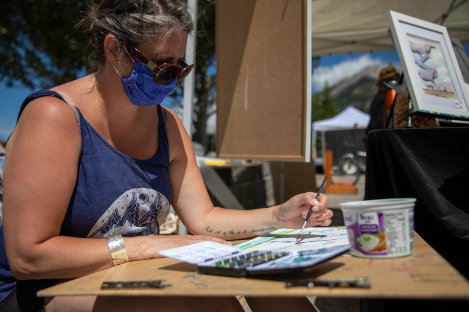 Artists of Elk Run (AER) member, Dawn Saunders Dahl paints with water colours during an artist's pop up market on Elk Run Boulevard on Saturday (July 18). Market dates are Aug. 1, Aug. 15 and Aug. 29.  EVAN BUHLER RMO PHOTO⁠