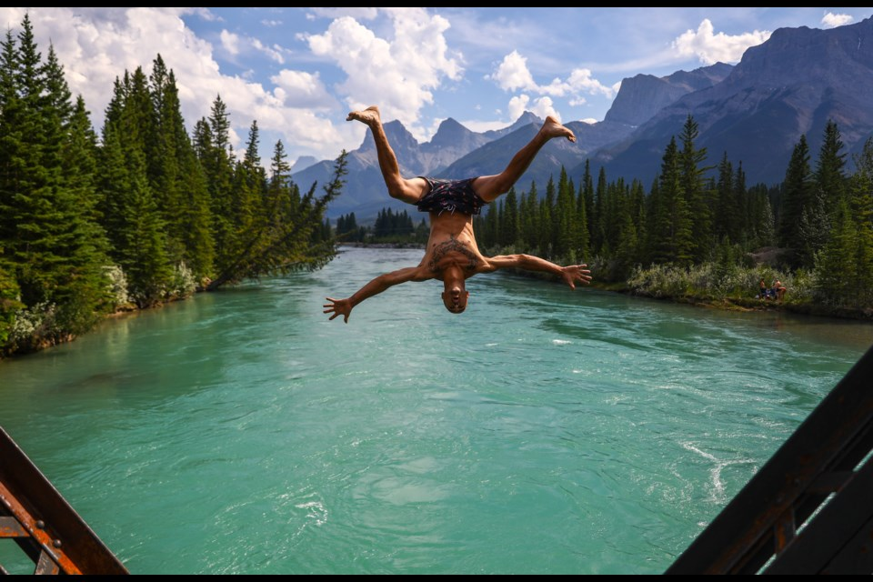Jamie Muller performs a stylized back flip from Engine Bridge into the Bow River on Saturday, Aug. 1, 2020. Environment Canada issued heat warnings for Banff National Park, Canmore, MD of Bighorn and Kananaskis Country, stating temperatures were expected to reach or exceed 29 C with overnight lows near 14 C. EVAN BUHLER RMO PHOTO⁠