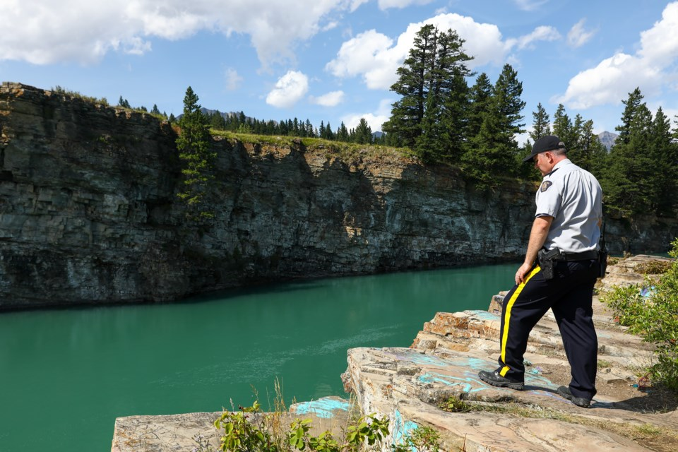 Cochrane RCMP Cpl. Troy Savinkoff looks out over a cliff along the Bow River where the suspected drowning victim Blessing Paul, 16, disappeared near the Seebe Dam, on Tuesday (Aug. 11). Since Saturday (Aug. 8) around 40 volunteers of the victim's family and emergency personnel have been searching the Bow River near Seebe, about 25 kilometres east of Canmore, where two helicopters, a dive team, and boat patrols have been combing since the weekend. EVAN BUHLER RMO PHOTO