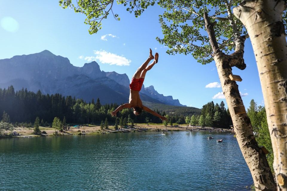 Noah Genier performs a back flip from a tree overhanging Quarry Lake on Saturday (Aug. 15). EVAN BUHLER RMO PHOTO