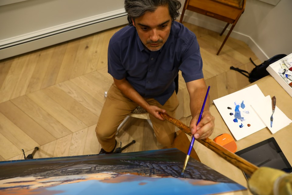 Banff artist Marcos Molina paints a large picture of Lake Louise at the Sideshow Gallery on Tuesday (Sept. 8). The gallery will host a closing reception for Molina's work on Tuesday (Sept. 15). EVAN BUHLER RMO PHOTO