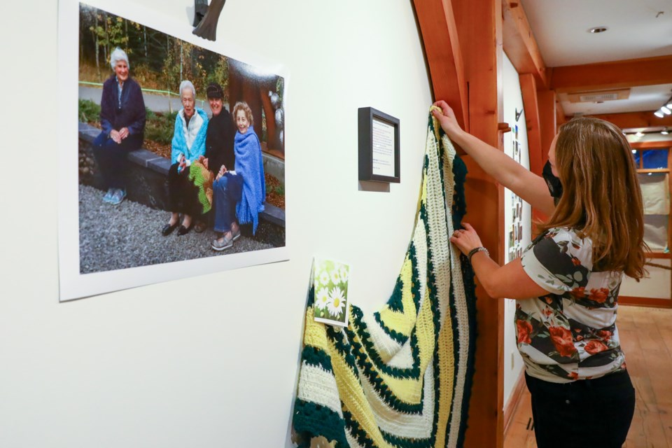 Canmore photographer Kristy Wolfe hangs up a prayer shawl as part of the Picture This: Stories of Lives Well Lived pop up galley at Stonewaters on Tuesday (Nov. 17). EVAN BUHLER RMO PHOTO