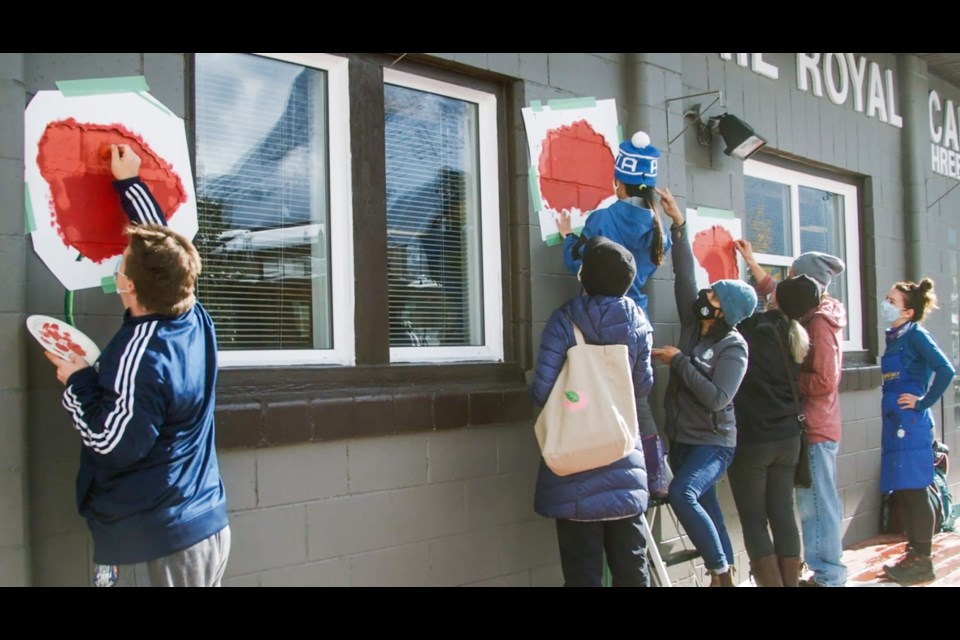 Participants from the Bow Valley Connections Centre (BVCC) paint a poppy mural under the guidance of Canmore artist Libby Amber Pryor. The mural is on the facade of the Canmore Legion as part of the Town of Canmore's Building Neighbourhoods Builds Community Project. SCREENGRAB SETH WILLIAMS