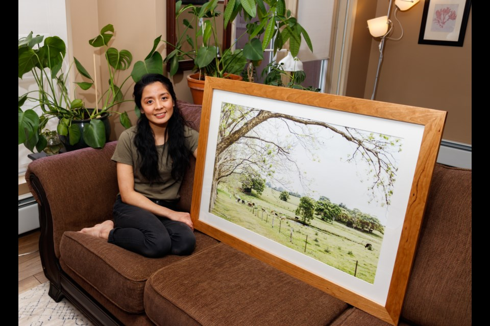 "Photographer Camille Santiago holds her piece that will be featured in Art for Australia ""The Farm,"" a photo of a farm in Byron Bay, New South Wales in her apartment on Sunday (Feb. 9). CHELSEA KEMP RMO PHOTO"