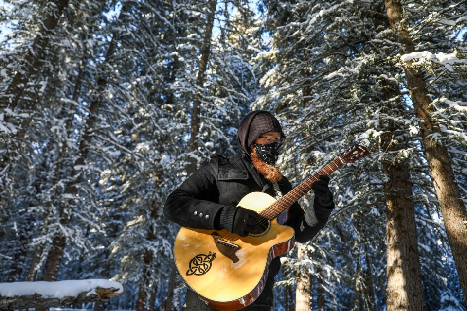 Kasey Nolan wears a musically inspired mask while playing guitar as a symbol of his recently released instrumental album The Voiceless. 	EVAN BUHLER RMO PHOTO
