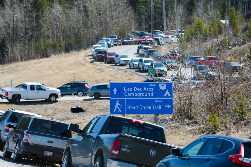 Several dozen cars park along the Lac des Arcs highway exit and along the road to the Heart Creek trail head parking lot on Saturday (April 17). The parking lot was full. EVAN BUHLER RMO PHOTO