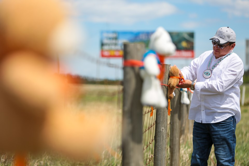 Chris Goodstoney a member of the Wesley Band of the Stoney Nakoda First Nation ties one of 215 teddy bears, in memory of the 215 children found in a mass grave on the grounds of the Kamloops Residential School, to a fence along the Trans-Canada Highway near the Stoney Nakoda Resort Casino on Tuesday (June 1). EVAN BUHLER RMO PHOTO