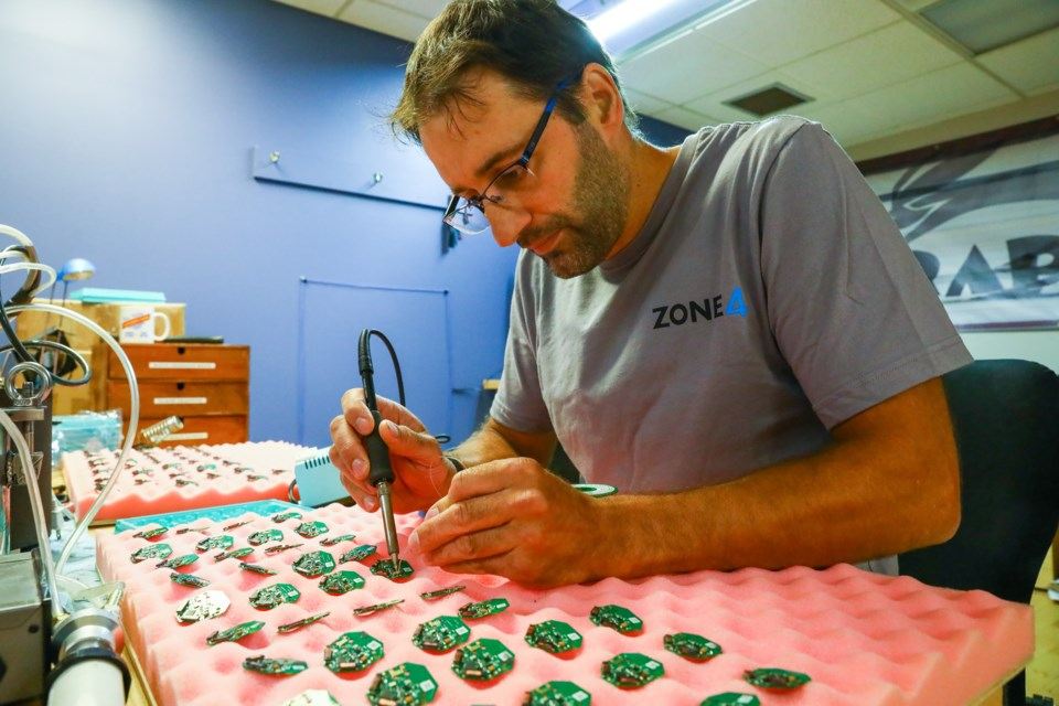 Dan Roycroft, founder of Zone4, solders one of the chips found in their timing devices on Tuesday (July 20). EVAN BUHLER RMO PHOTO