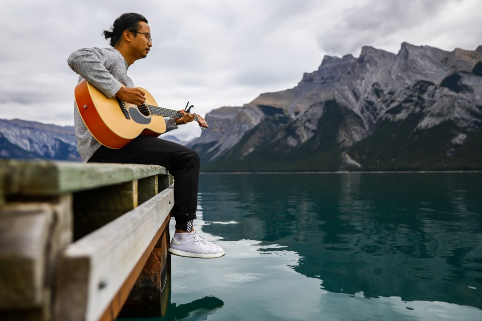 John Garcia plays guitar and sings at the end of the dock at Lake Minnewanka in Banff National Park on Thursday (Sept. 2). EVAN BUHLER RMO PHOTO
