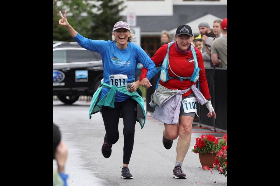Lori Hanson, left, and Nancy Freiday cross the finish line together in the half marathon at the 2021 Banff Marathon on Sept. 12.  GREG COLGAN/RMO PHOTO