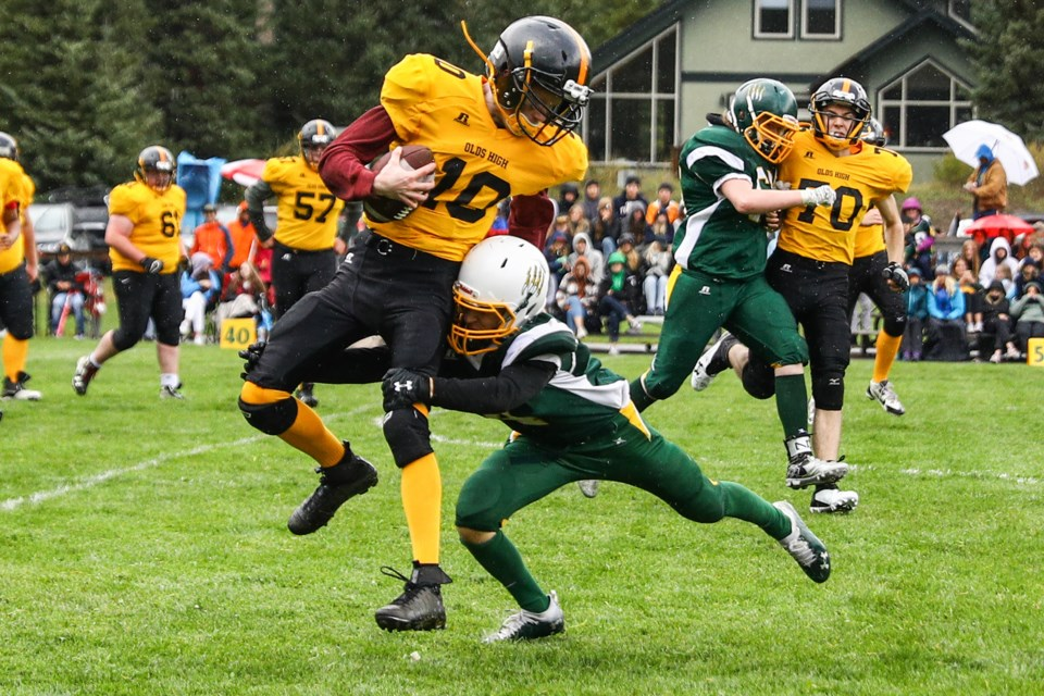 Even Odyakmaz tackles the Olds Spartans quarterback after being flushed out of the pocket during the Wolverines season opener against the Olds Spartans at Millennium Field on Saturday (Sept. 18). EVAN BUHLER RMO PHOTO