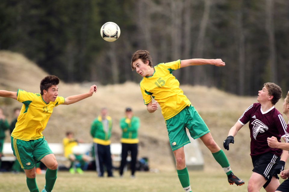Canmore Collegiate High School's Xavier McKeever, left, prepares to jump to catch a headed ball from Adam Weatherhog at Millennium Field in Canmore in 2019. RMO FILE PHOTO