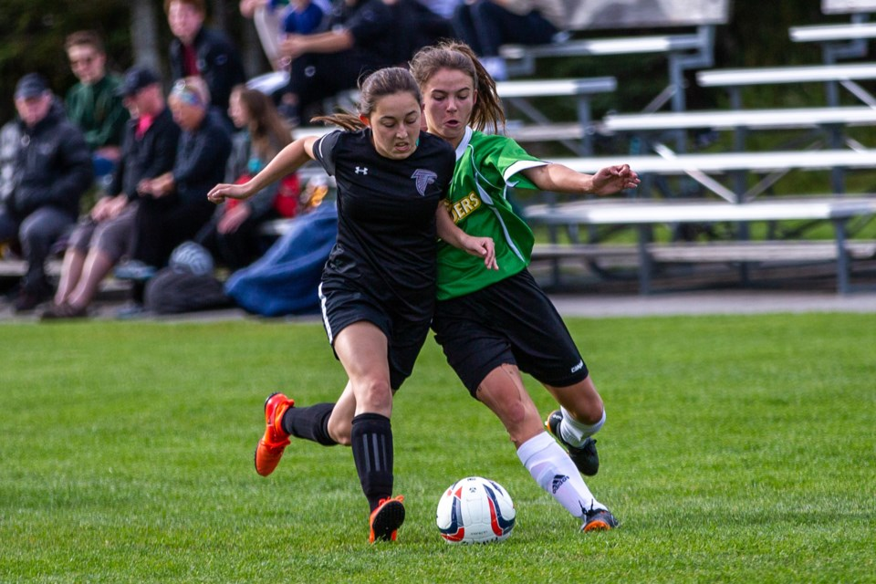 Canmore Wolverine, Anna Jasinsky, right, is pushed off the ball by a Falcons defender during Tuesday's (Sept. 17) game at Millennium Field. Evan Buhler RMO Photo