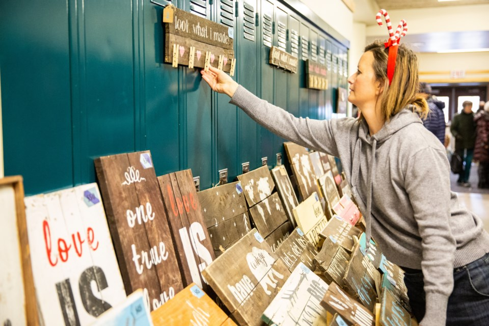Vendor, Vic McCulloch hangs up a sign for sale at the 24th Canmore Christmas Artisans' Market held at Canmore Collegiate High School in 2019. EVAN BUHLER RMO FILE PHOTO