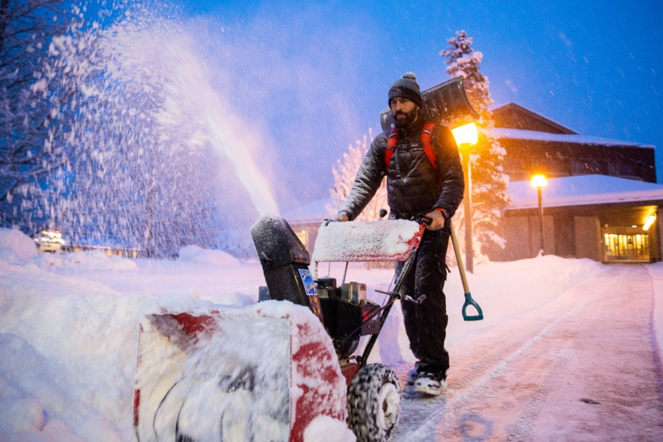 Carlos Aulos clears the sidewalk in front of the Canmore Provincial Courthouse on Saturday (Dec. 21) morning. Canmore received more than 20 cm of snow since the snow storm started early on Friday morning. EVAN BUHLER RMO PHOTO