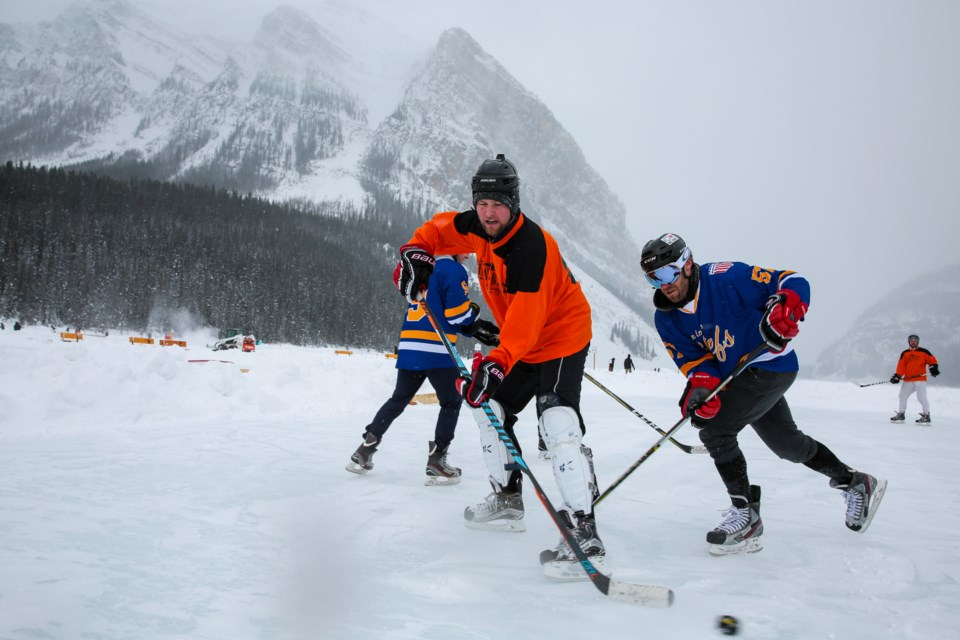 Under a heavy snowfall, Peter McCarthy of Mackenzie Investments passes the puck past the Chiefs Shane Hynes during a round robin game at the 2020 Lake Louise Pond Hockey Classic last February. The Chiefs took home the title for the ninth year out of 11 years the tournament has been operating. EVAN BUHLER RMO PHOTO
