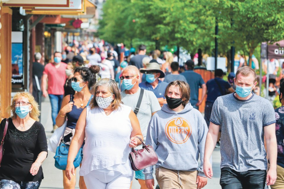 Tourists walk along Banff Avenue wearing face masks on Saturday (Aug. 1). Friday marked the first day the town's mandatory mask by-law took effect. EVAN BUHLER RMO PHOTO