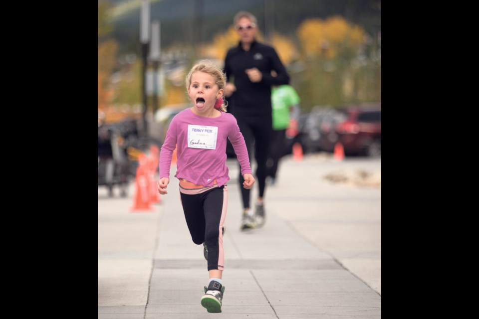 Abagail Guss, centre, puts on a shocked face as she beats her father Tim across the finish line for the third annual Canmore Terry Fox Run at Elevation Place in Canmore  in 2016. RMO FILE PHOTO