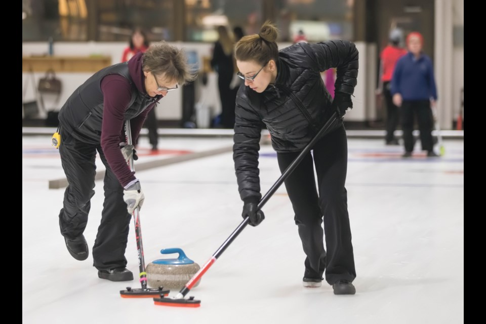 Skip Karen Dreaver, left, and lead Stephanie Olthuis sweep a rock during a bonspiel at the Canmore Golf and Curling Club. The local club will host the 2021 Canadian Mixed Curling Championship from Nov. 7-15, 2020. RMO FILE PHOTO
