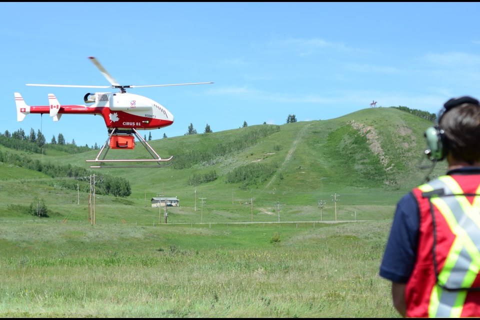 Principal Investigator Wade Hawkins watches the Swiss drone carry live viral test kits for the pilot project to deliver test kits from rural areas to urban centres, launched in Stoney Nakoda Nation from the Morley townsite on June 25, 2020.