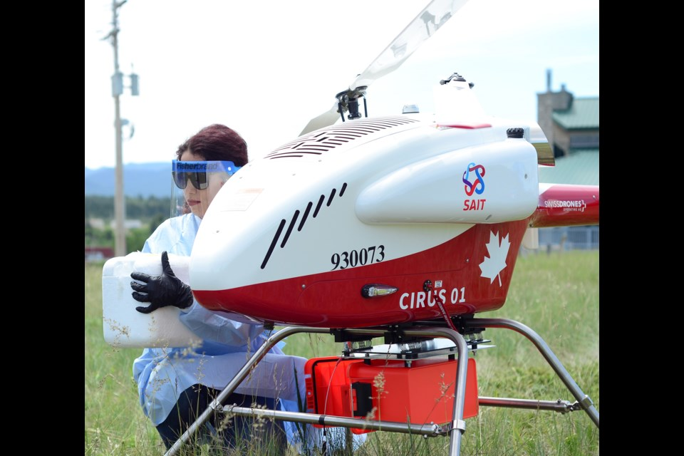 Stoney Health Authority officials participate in the pilot project attaching live viral test kits to the bottom of the $650k Swiss drone. The drone flew to the Ghost Lake Reservoir and back for the launch.  JENNA DULEWICH RMO PHOTO