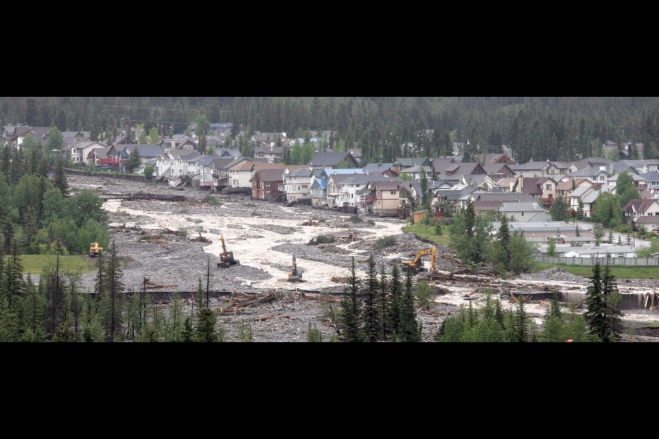 Looking up Cougar Creek as it covers the Trans-Canada Highway with many of the worst damaged houses lining the flood water's path on the creek's east bank in 2013. RMO FILE PHOTO