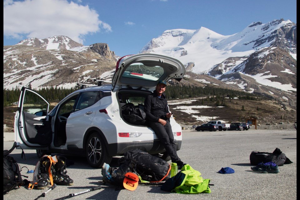 Greg Hill leans against his electric car on a mission to ski Mount Athabasca. ANTHONY BONELLO PHOTO