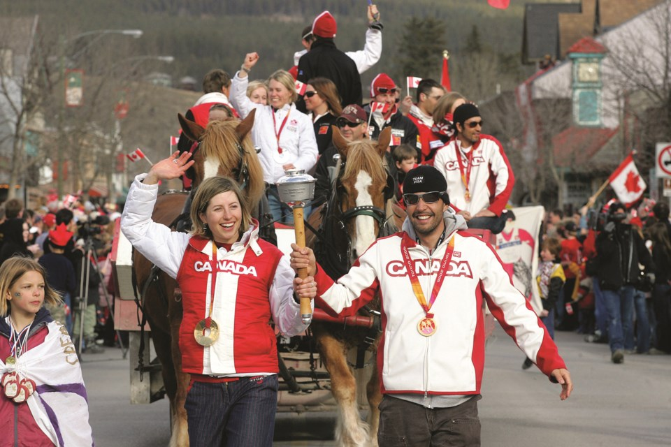 In 2006, Olympic cross-country ski champion, Chandra Crawford, and four-time Paralympic medallist, Brian McKeever, wave to fans as they lead an Olympic homecoming parade down Canmore's Main Street. RMO FILE PHOTO
