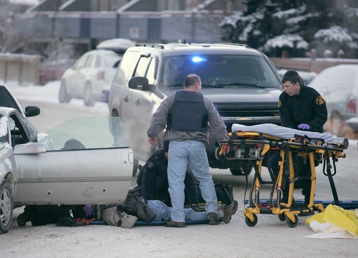 An armed robbery suspect is treated by EMS after being shot by Canmore RCMP in connection with three robberies in three days. Eyewitness accounts say the male fired two shots