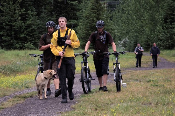 Conservation officer Brodie Rundel leads a group of cyclists from the end of the Highline mountain bike trail to the dog park following a cougar attack on their dog Monday
