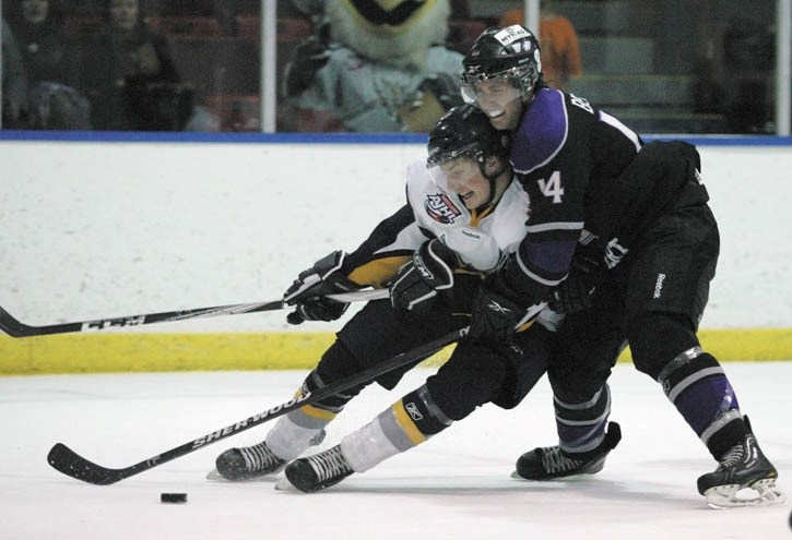 Canmore's John Stevens tries to fight off a check by St. Albert's Ryan Berlin as the Eagles take on the Steel at the Canmore Rec Centre Friday night (Oct. 7). St. Albert won