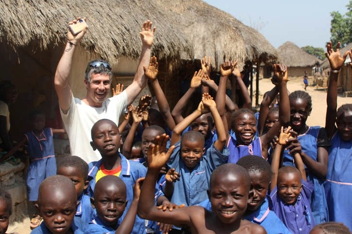 Alistair Darichuk is greeted by several schoolchildren in Sierra Leone. He and several Bicycle Cafe employees took part in a 600 km Cause Canada expedition across the country.