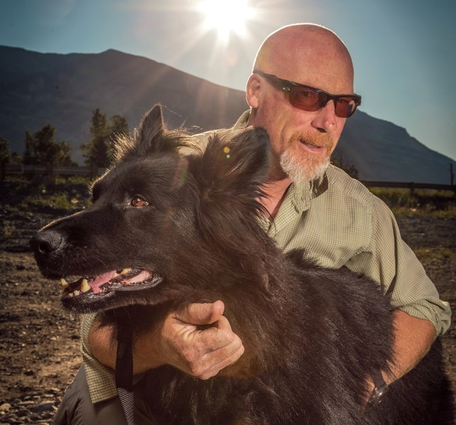 Mike Henderson, warden and dog handler for Parks Canada in Banff, poses with Cazz near Cougar Creek in Canmore on Tuesday (Aug. 2). Henderson, already a decorated and award