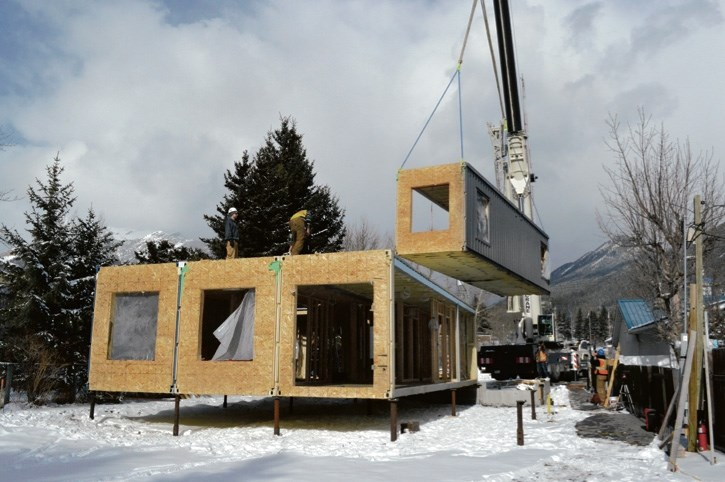 Clockwise from top: a sea can modular housing unit being installed in the community of Exshaw in February.