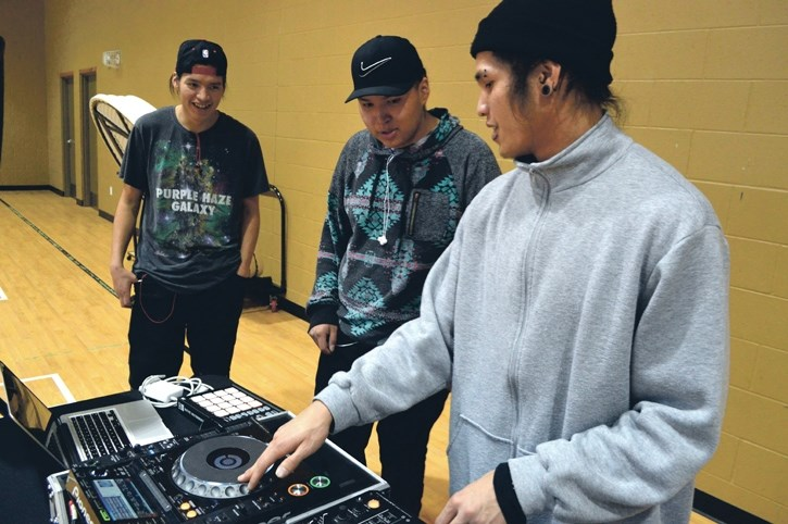 Gene 'Gomo' Cabarroguis, right, shows how to scratch and make beats using a turntable to Stoney Nakoda's Dace Hunter and Kevin Fox at the Morley's ReFreshed After-School Hip