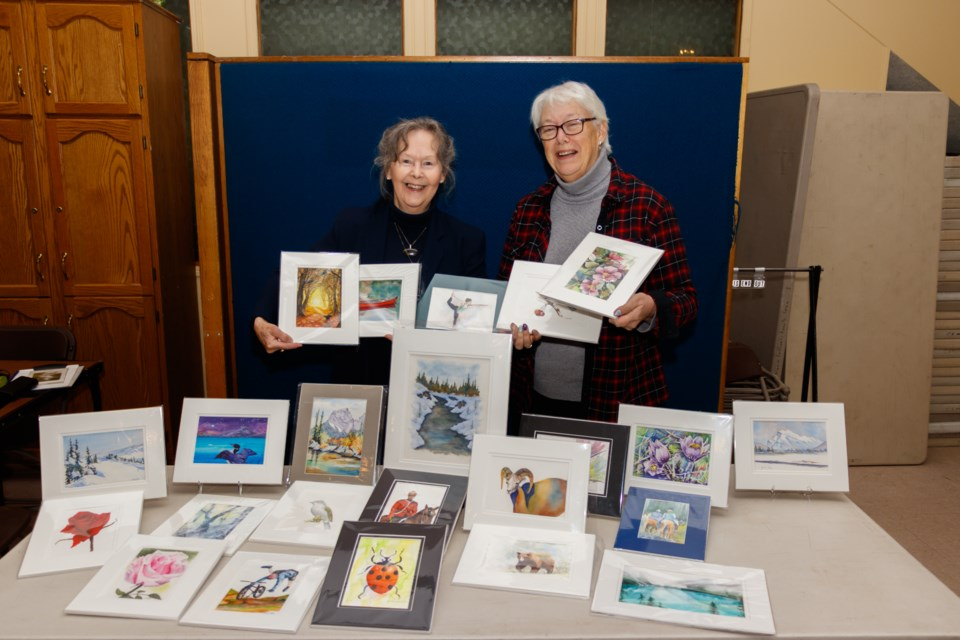 Artists Donna Jo Massie, left, and Maureen McKay showcase a selection of artwork that will be featured at the upcoming The Arts and Song Fundraiser on Thursday, Oct. 24, 2019. (Photo by Chelsea Kemp RMO PHOTO)