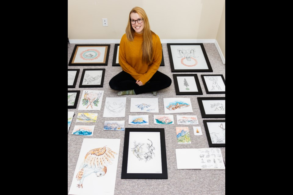 Canmore artist Emily Beaudoin sits surrounded by a selection of her works on Monday, Dec. 2, 2019. CHELSEA KEMP RMO PHOTO