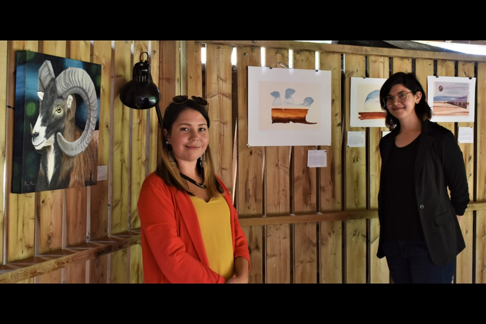 Visual artists Kas Rea, left, and Julia pose with some of their artworks after the residency in the Bunkhouse Project last month.
