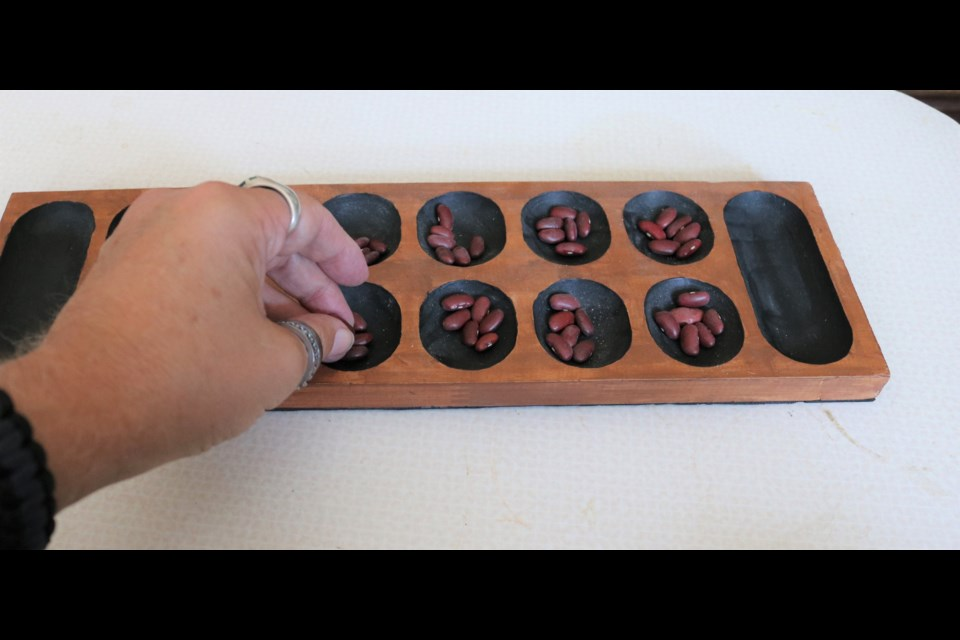 There are a number of games in the mancala family with use a board of pits with plays moving beads or beans or shells around the board.