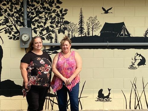 Heather Gawrelitza, right, posed for a photograph with Carrie Olson who finished the wall mural that was painted on the shower building at the Preeceville Wildlife campground.