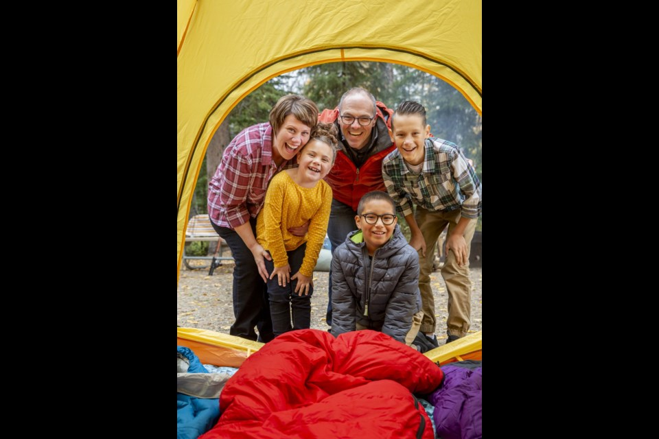 A family enjoys a camping adventure at Beaver Glen Campground in Prince Albert National Park.