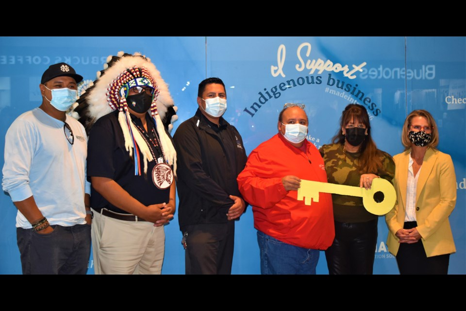 Battlefords Agency Tribal Chiefs Executive Director Neil Sasakamoose, fourth left, receives the ceremonial key for the Nikihk store from Midtown Plaza specialty leasing manager Linda Young. Others in photo are, from left, Cree language translator Randy Morin, Federation of Sovereign Indigenous Nations Second Vice-Chief David Pratt, Moosomin First Nation Chief Brad Swiftwolfe and Midtown Plaza general manager Janice Sander.