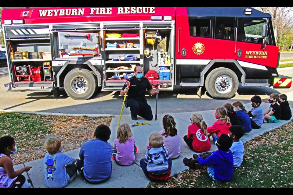 Weyburn career firefighter Marc Schweitzer explained what some of the various tools and gadgets are on a fire truck, during a visit with the Grade 1 class at St. Michael School on Wednesday during Fire Prevention Week.