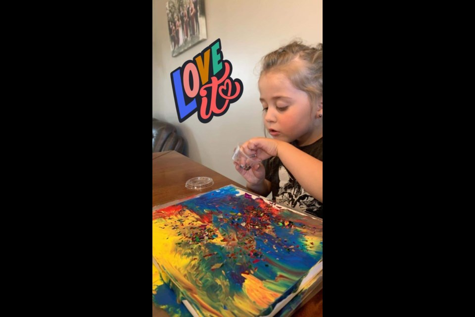 Aurora concentrating on her painting for a Wilkie Library craft project.